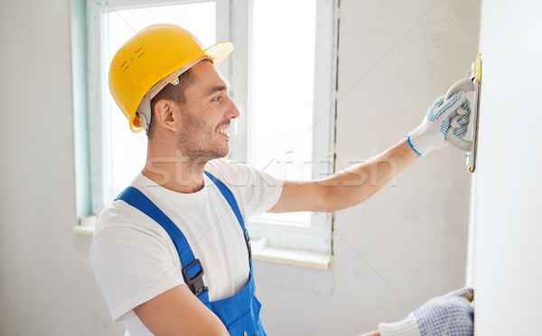 smiling builder with grinding tool indoors Stock photo © dolgachov