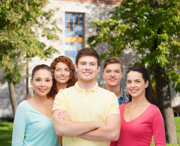 group of smiling teenagers over campus background Stock photo © dolgachov