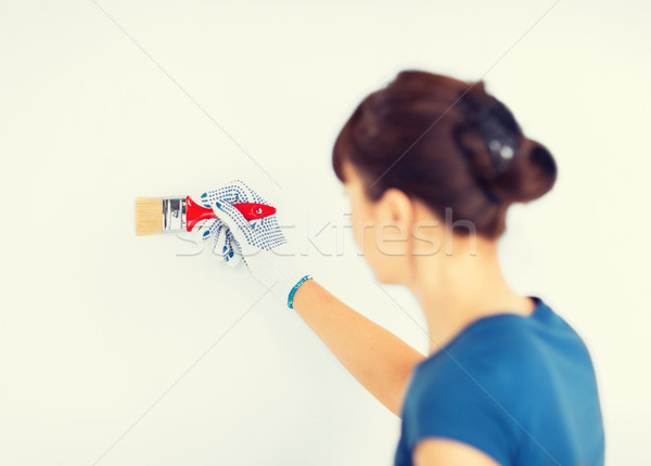 woman with paintbrush colouring the wall Stock photo © dolgachov
