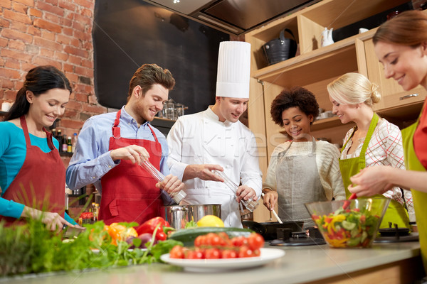 happy friends and chef cook cooking in kitchen Stock photo © dolgachov