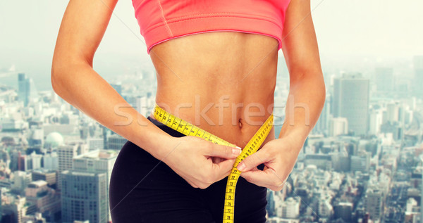 close up of female hands measuring waist Stock photo © dolgachov