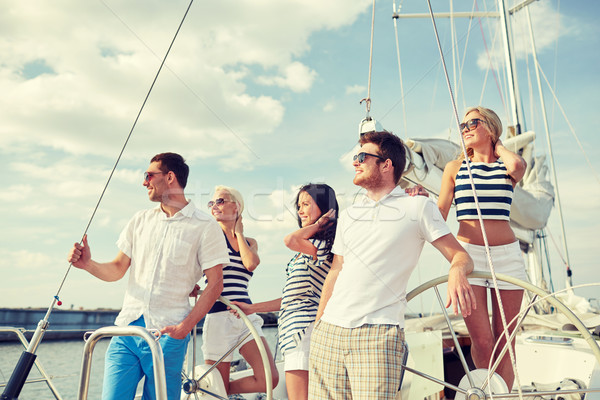 smiling friends sailing on yacht Stock photo © dolgachov