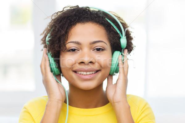 happy woman with headphones listening to music Stock photo © dolgachov