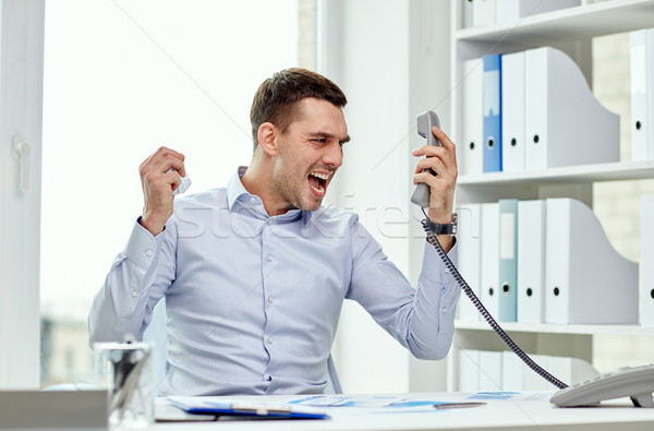 furious businessman calling on phone in office Stock photo © dolgachov