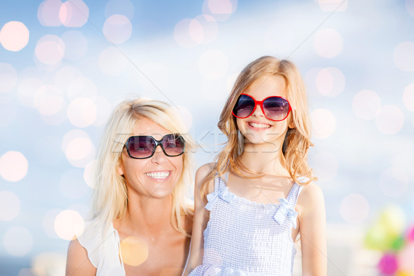 mother and child in sunglasses over blue lights Stock photo © dolgachov