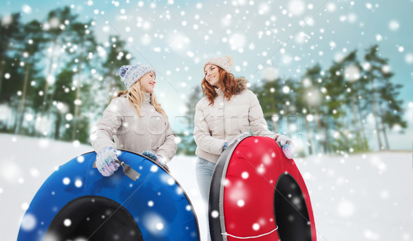 happy girl friends with snow tubes outdoors Stock photo © dolgachov