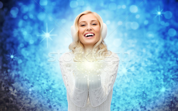 woman in winter earmuffs with fairy dust on palms  Stock photo © dolgachov