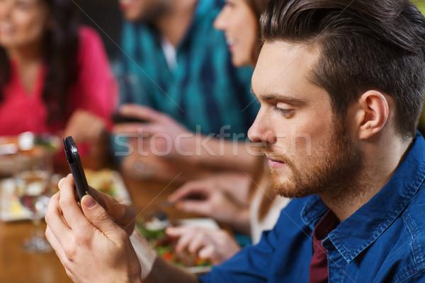Uomo smartphone amici ristorante tempo libero tecnologia Foto d'archivio © dolgachov