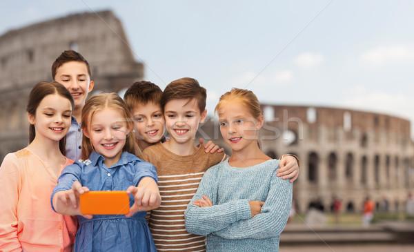 children talking smartphone selfie over coliseum Stock photo © dolgachov