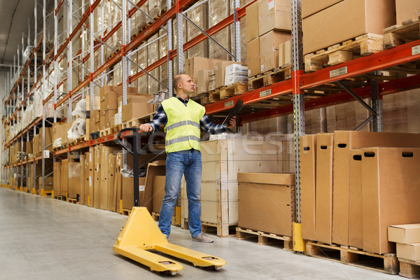 man with loader and clipboard at warehouse Stock photo © dolgachov