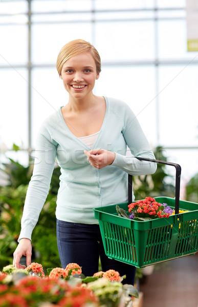 happy woman with basket choosing flowers in shop Stock photo © dolgachov