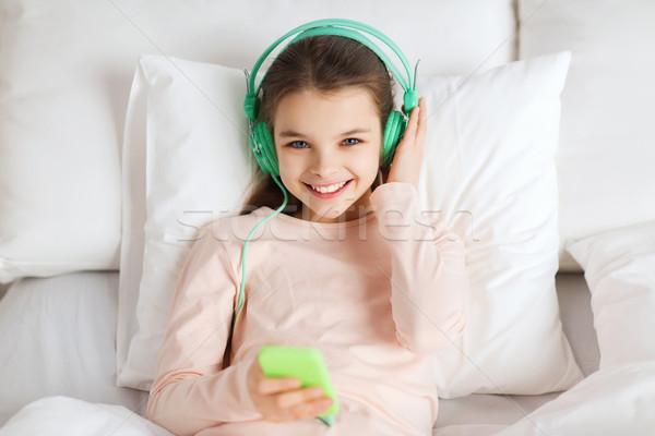 Happy girl bed smartphone domu ludzi dzieci Zdjęcia stock © dolgachov