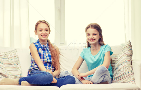 happy little girls sitting on sofa at home Stock photo © dolgachov