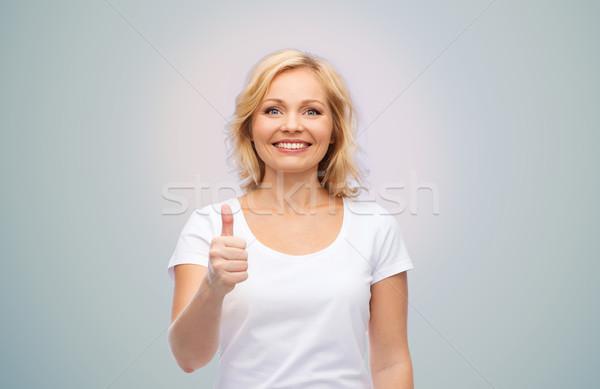 Stock fotó: Mosolygó · nő · fehér · póló · mutat · remek · kézmozdulat