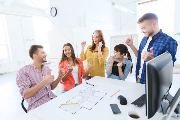 happy creative team celebrating success at office Stock photo © dolgachov