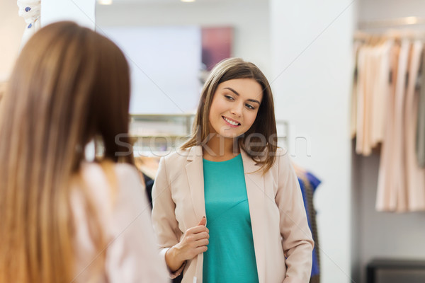 happy woman posing at mirror in clothing store Stock photo © dolgachov