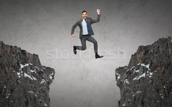 happy smiling businessman jumping between rocks Stock photo © dolgachov