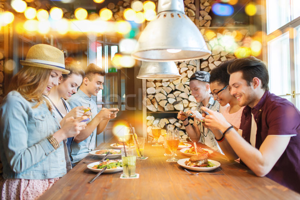 happy friends with smartphones picturing food Stock photo © dolgachov