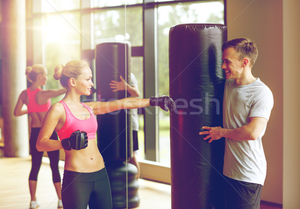 smiling woman with personal trainer boxing in gym Stock photo © dolgachov