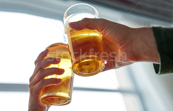 close up of hands clinking beer glasses at pub Stock photo © dolgachov