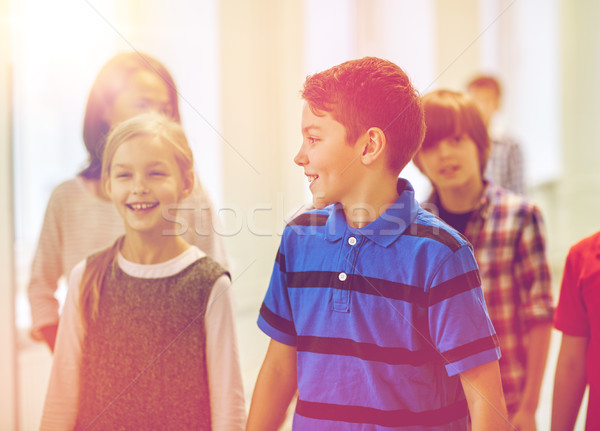 group of smiling school kids walking in corridor Stock photo © dolgachov