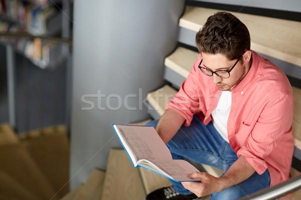 Diák fiú fiatalember olvas könyv könyvtár Stock fotó © dolgachov
