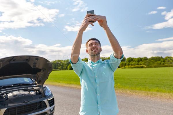 Uomo smartphone auto rotta campagna strada viaggio Foto d'archivio © dolgachov