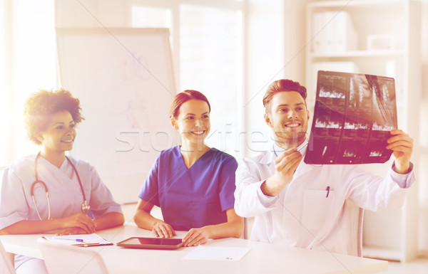 group of happy doctors discussing x-ray image Stock photo © dolgachov