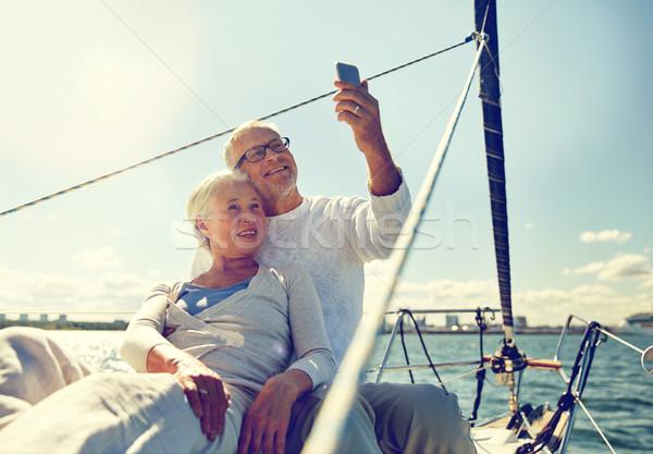 senior couple taking selfie by smartphone on yacht Stock photo © dolgachov