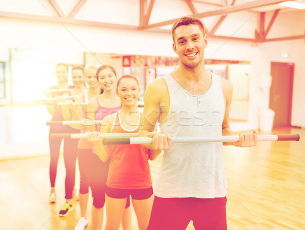group of smiling people working out with barbells Stock photo © dolgachov