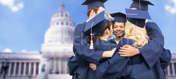happy students or bachelors hugging Stock photo © dolgachov