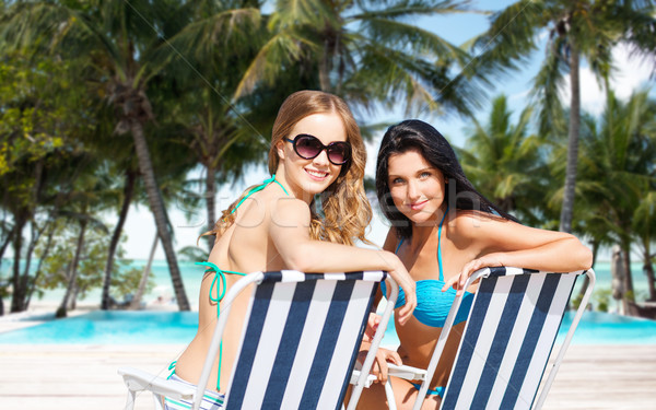 happy women sunbathing in chairs on summer beach Stock photo © dolgachov