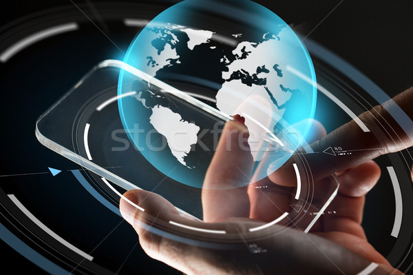 Stock photo: close up of hands with smartphone and earth
