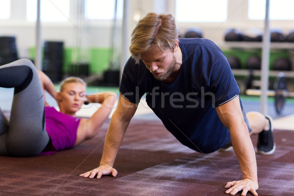 man exercising and doing straight arm plank in gym Stock photo © dolgachov