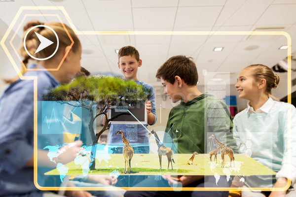 group of happy children with tablet pc at school Stock photo © dolgachov