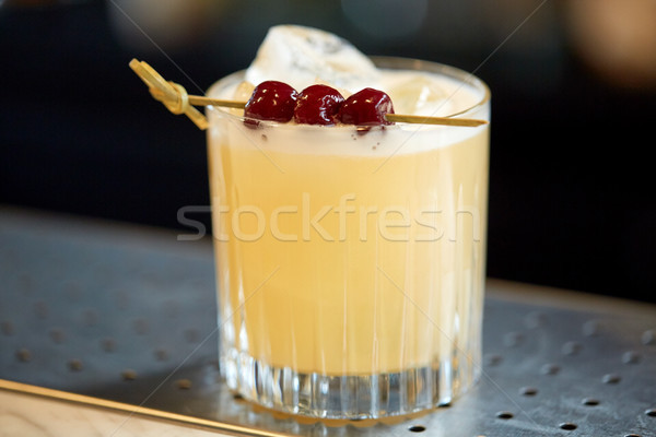 glass of cocktail with cherries at bar Stock photo © dolgachov
