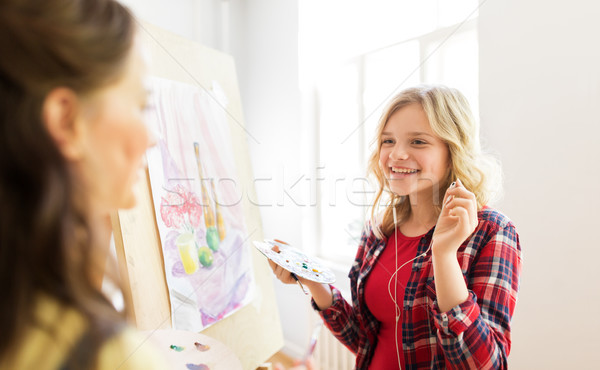 student girls with easel painting at art school Stock photo © dolgachov