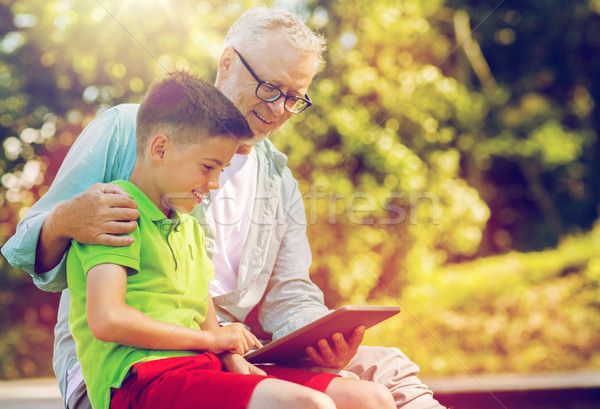 happy grandfather and boy with tablet pc outdoors Stock photo © dolgachov