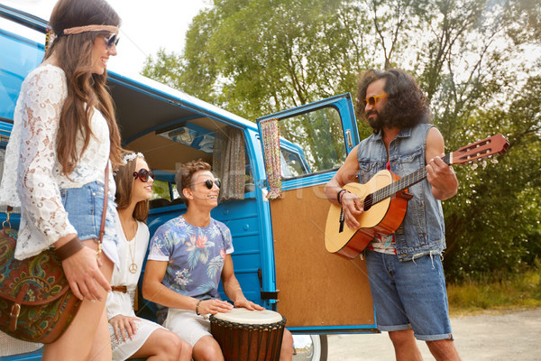 happy hippie friends playing music in minivan Stock photo © dolgachov