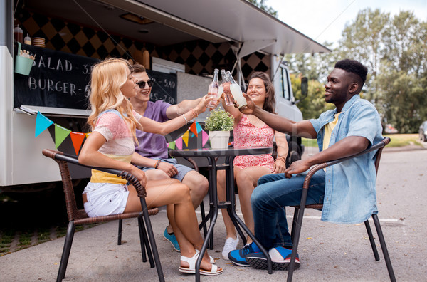 friends clinking bottles with drinks at food truck Stock photo © dolgachov