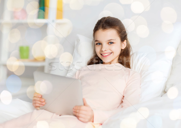 happy girl in bed with tablet pc over lights Stock photo © dolgachov
