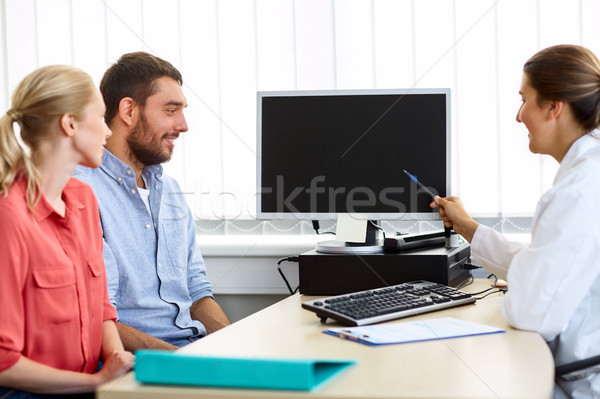 couple and doctor pointing at computer at clinic Stock photo © dolgachov