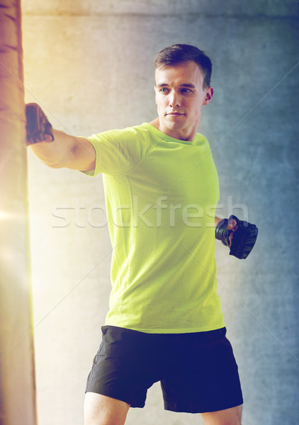 young man in gloves boxing with punching bag Stock photo © dolgachov