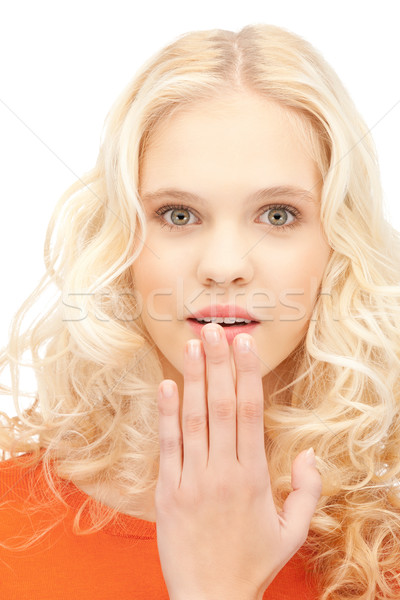 teenage girl with palms over mouth Stock photo © dolgachov