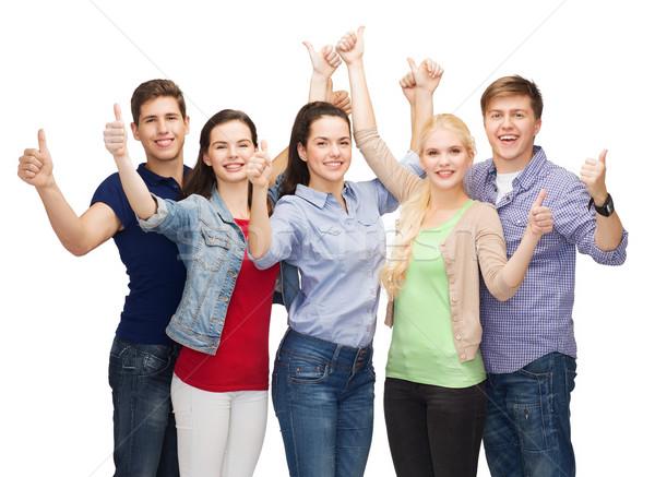 Groep glimlachend studenten tonen onderwijs Stockfoto © dolgachov