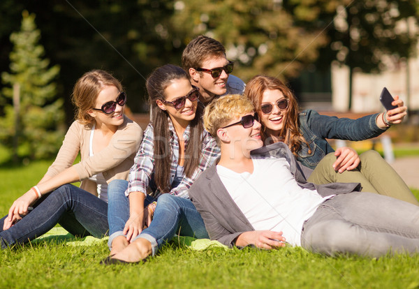 teenagers taking photo outside with smartphone Stock photo © dolgachov