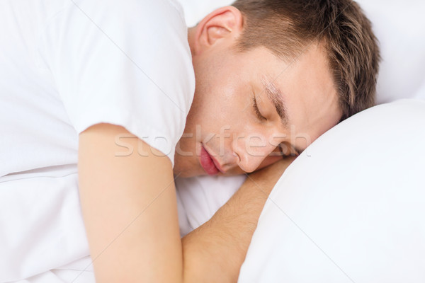 handsome man sleeping in bed Stock photo © dolgachov