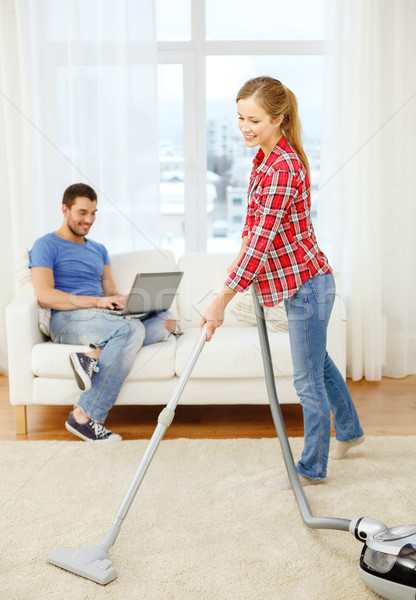 smiling woman with hoover and man with laptop Stock photo © dolgachov
