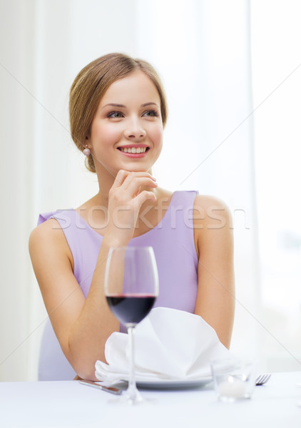 smiling woman with glass of whine waiting for date Stock photo © dolgachov