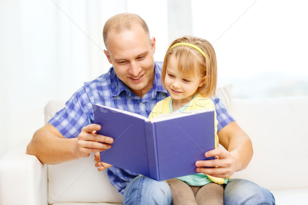 smiling father and daughter with book at home Stock photo © dolgachov
